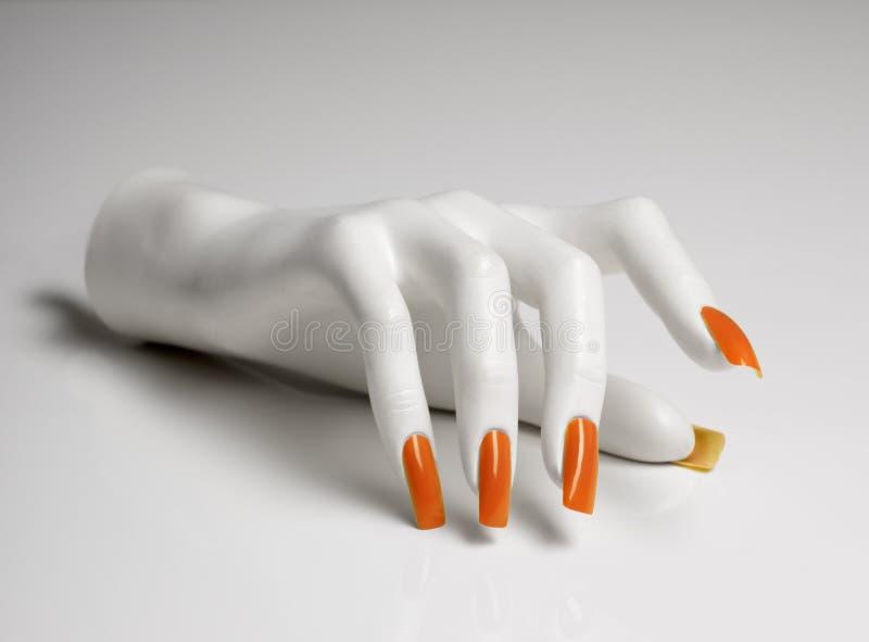 Skyltdockahanden med perfekt manikyr och apelsinen spikar polermedel arkivfoto