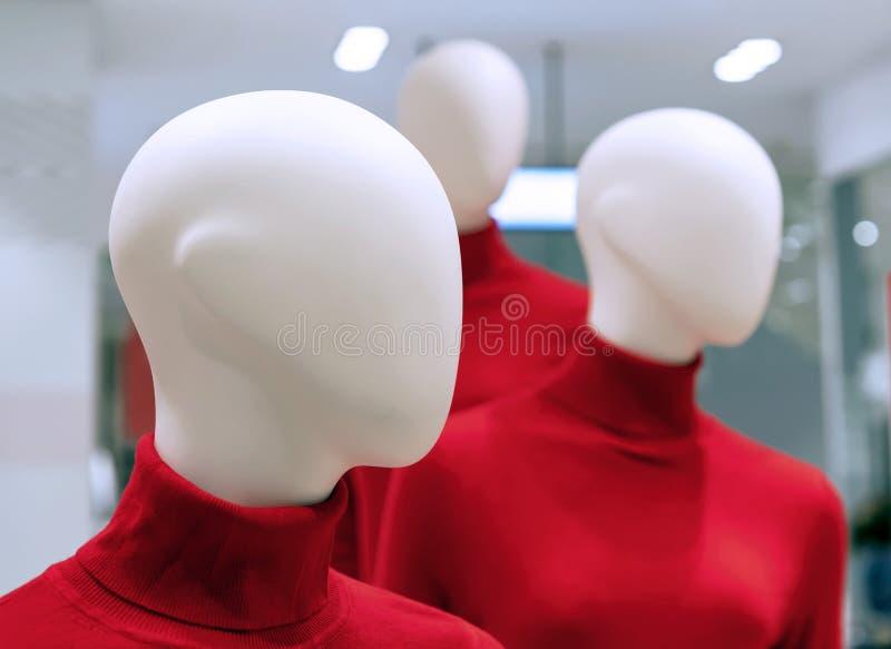 Skyltdockor i röda tröjor i inre av ett bekläda lager arkivfoto