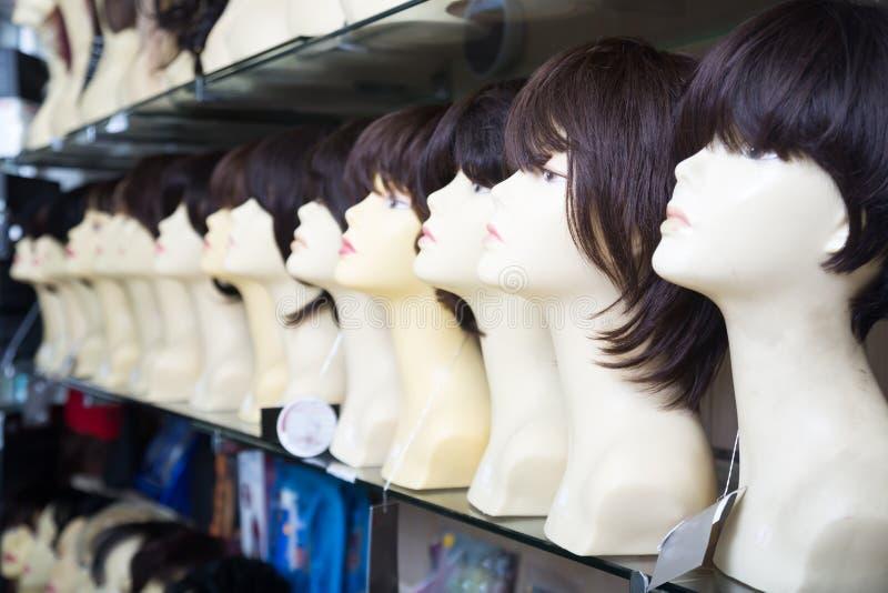 Skyltdockor med peruker på hyllor av hårsalongen royaltyfri fotografi