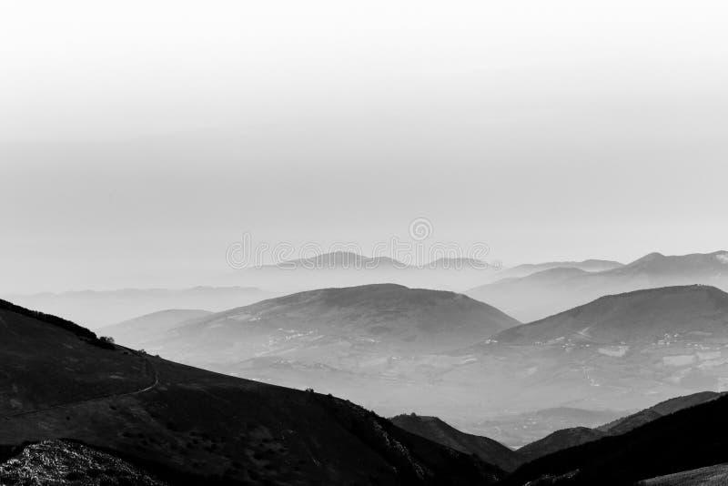 Skymning med berglager och mist dem emellan fotografering för bildbyråer