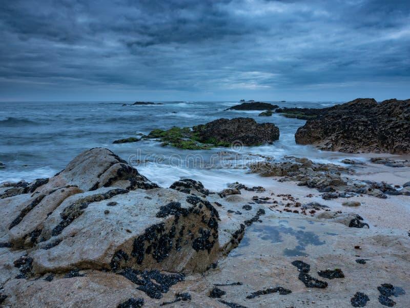 Skymning på den steniga stranden med dramatiska moln och mörk lynnig himmel exponering long arkivfoto