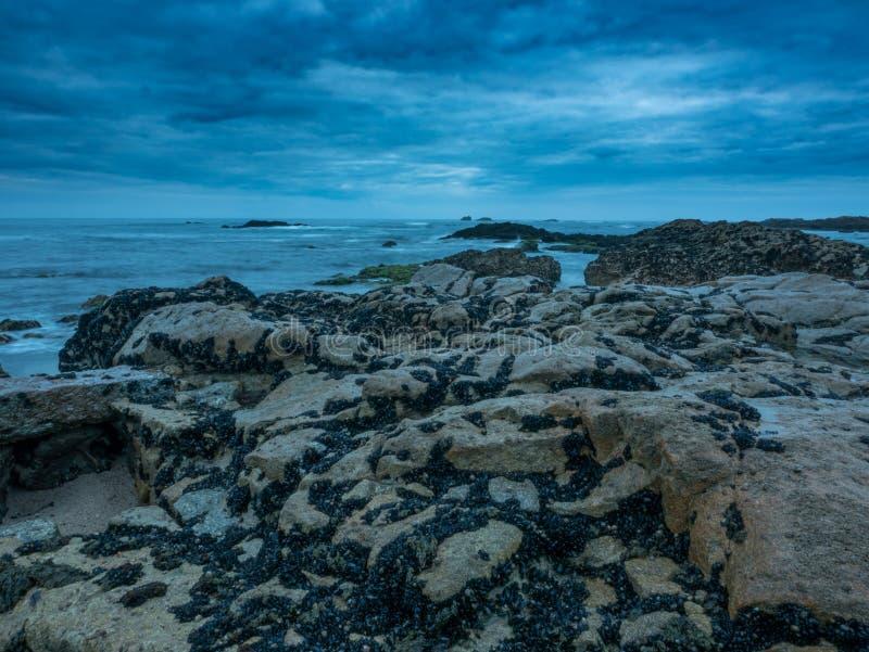 Skymning på den steniga stranden med dramatiska moln och mörk lynnig himmel exponering long royaltyfri bild