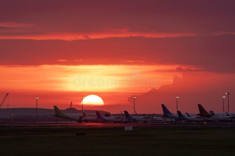 Skymninghimlen i en flygplats dekoreras med solnedgångar som startar att sjunka den guld- apelsinen med konturer av flygplanaktiv arkivbild