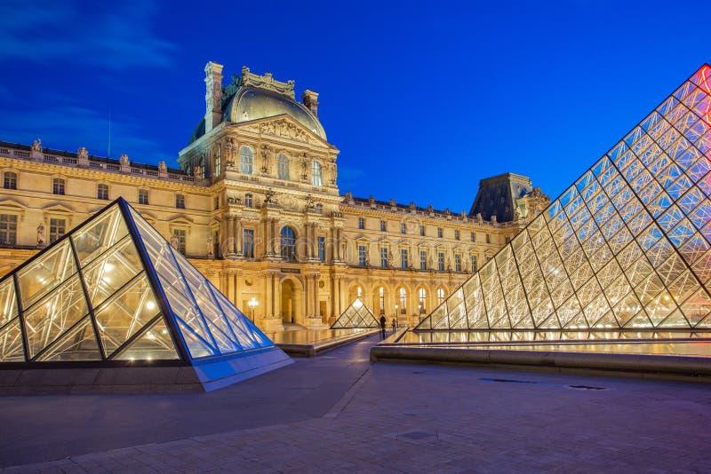 Skymningsikt av den Paris staden med Louvremuseet i Frankrike arkivbilder