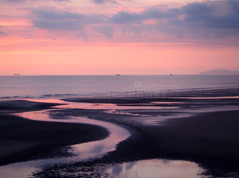 skymningsikt av en m?rk strand med en rosa himmel efter solnedg?ng med bl?a moln reflekterade i vattnet p? l?gvatten och ett lugn arkivbild
