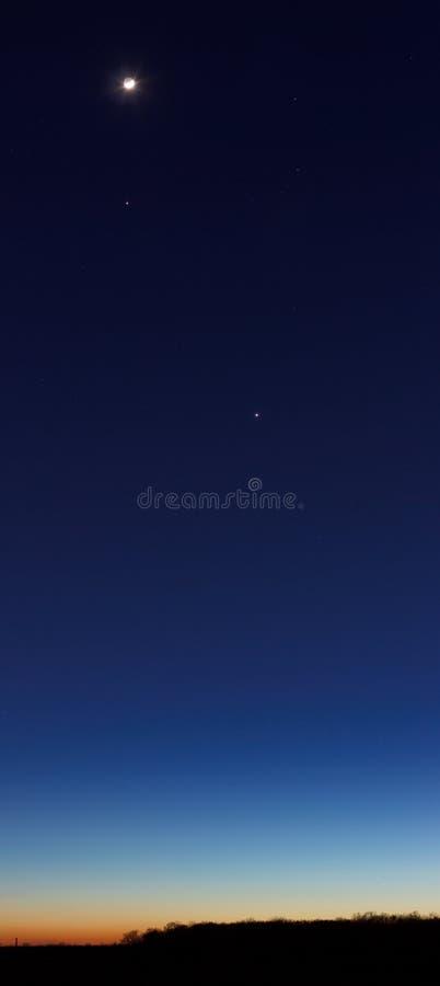 Skymningsky med planet och moonen royaltyfria foton