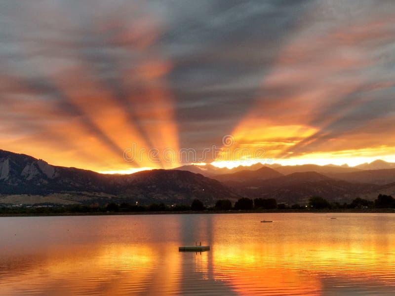 Skymningstrålar av ljus som bakifrån strålar bergsjösolnedgång fotografering för bildbyråer