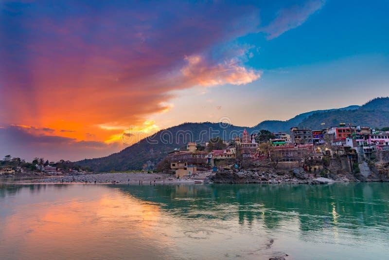 Skymningtid på Rishikesh, den heliga staden och loppdestinationen i Indien Färgrik himmel och moln som reflekterar över Gangeset  royaltyfria foton