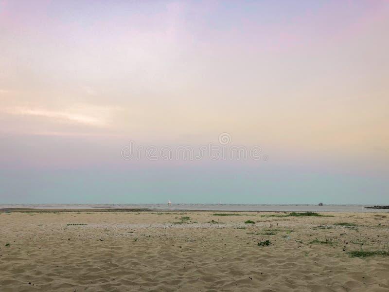 Skymningtid på stranden med sand och havet landskap backgroun royaltyfria bilder