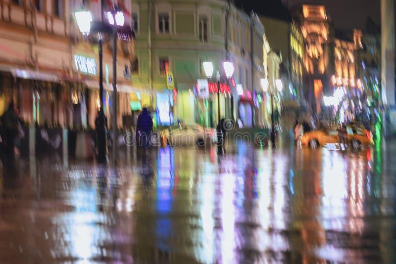 Skynda sig ungdomarunder paraplyer på en regnig natt i gata av staden Livlig belysning från lyktor och att shoppa arkivfoton