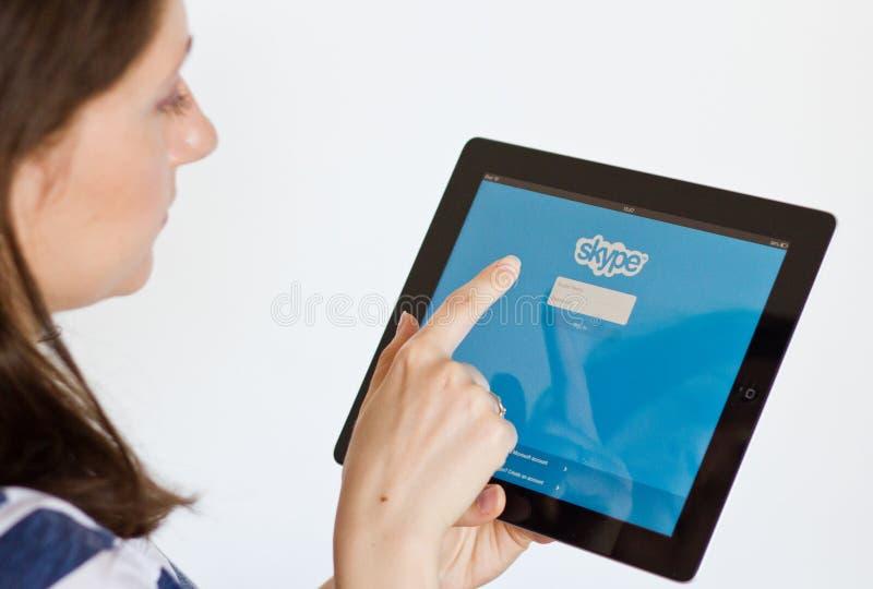 Skype. Woman logs in on Skype free communications network on digital tablet
