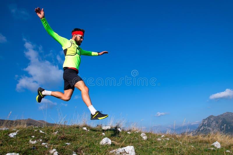 Skyrunner durante il salto in discesa nei prati della montagna fotografie stock