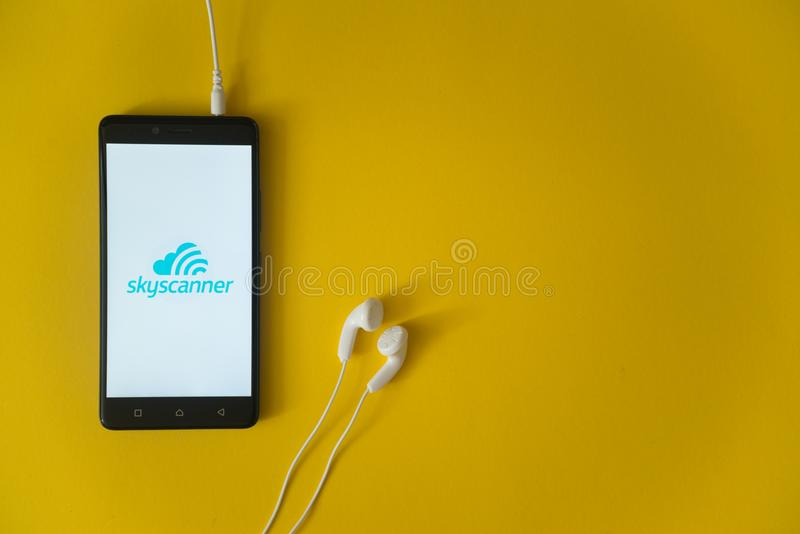 Skyscannerembleem op het smartphonescherm op gele achtergrond royalty-vrije stock afbeeldingen