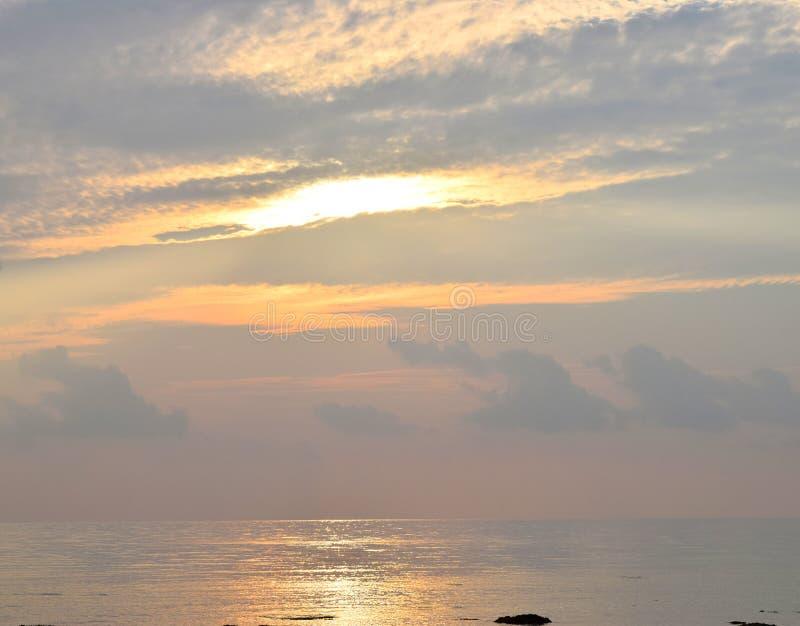 Skyscape при яркие золотые желтые солнечные лучи излучая в облачное небо на времени восхода солнца над океаном - естественной пре стоковые фотографии rf