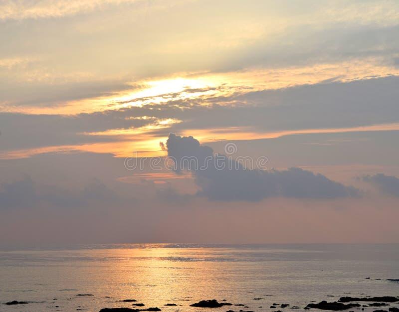 Skyscape с яркими золотыми желтыми теплыми цветами в облачном небе на времени восхода солнца над океаном - естественной предпосыл стоковые фото