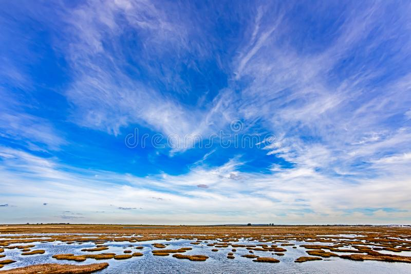Skyscape of blue sky and clouds above salt marsh stock photography