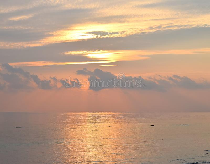 Skyscape with Bright Golden Yellow Warm Colors in Cloudy Sky at time of Sunrise over Ocean - Natural Background. This is a photograph of golden yellow colors in stock photos