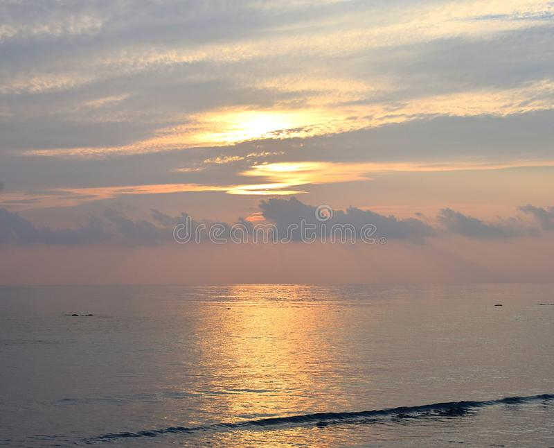 Skyscape with Bright Golden Yellow Warm Colors in Cloudy Sky at time of Sunrise over Ocean - Natural Background. This is a photograph of golden yellow colors in royalty free stock photo