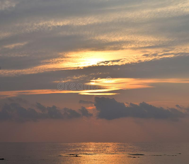Skyscape with Brilliant Golden Yellow Colors in Cloudy Sky at time of Sunrise over Ocean - Natural Background. This is a photograph of golden yellow colors in stock photo