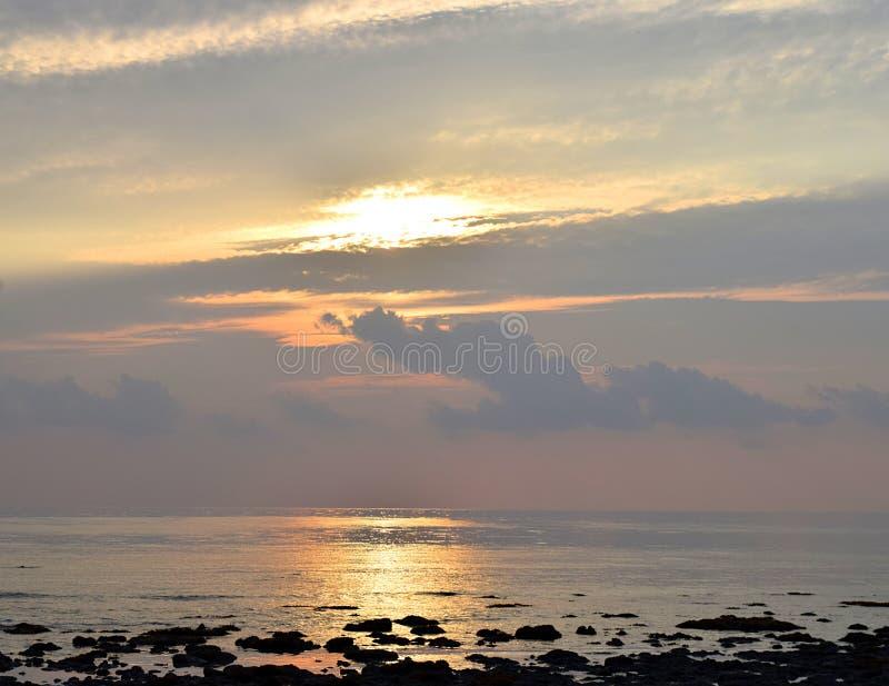 Skyscape met Heldere Gouden Gele Zonnestralen die in Bewolkte Hemel in tijd van Zonsopgang over Oceaan uitstralen - Natuurlijke A royalty-vrije stock afbeeldingen