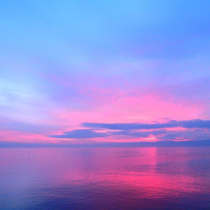 Skyscape rosado en el lago Lemán imagenes de archivo