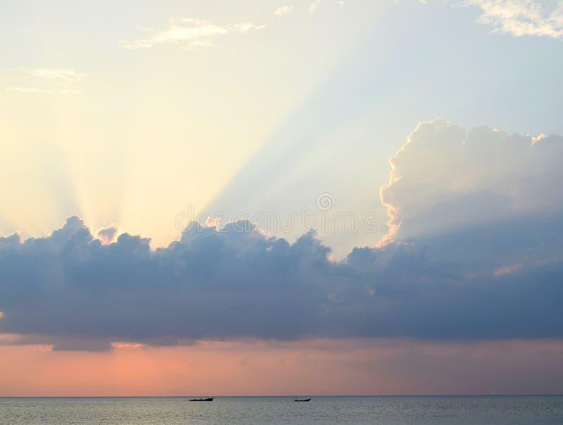 Skyscape in tijd van Zonsondergang - Heldere Gouden Zonnestralen die door Wolken met Oranje hemel bij Horizon over Blauw Zeewater stock fotografie