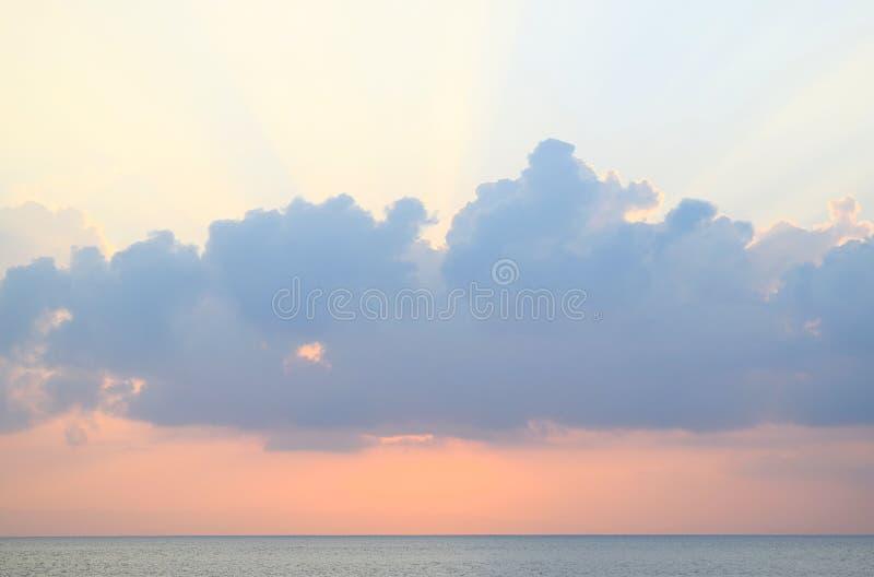 Skyscape in tijd van Zonsondergang - Schemerige Heldere Zonnestralen die door Wolken met Oranje hemel bij Horizon over Blauw Zeew stock foto