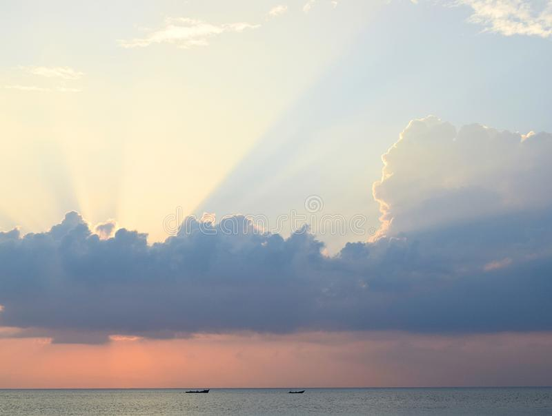 Skyscape at time of Sunset - Bright Golden Sunrays spreading through Clouds with Orange sky at Horizon over Blue Sea Water stock photography