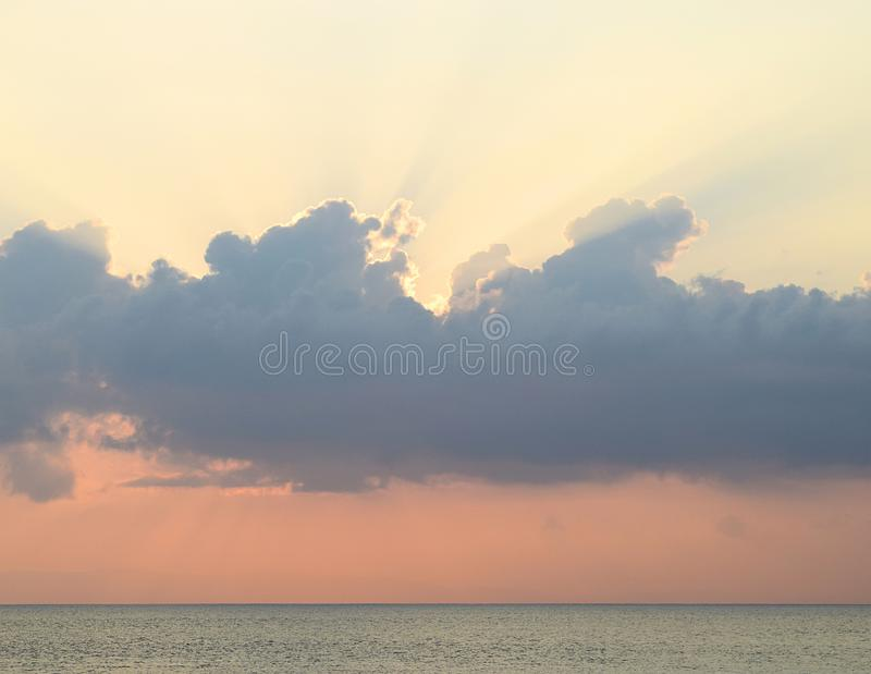Skyscape at time of Sunset - Crepuscular Bright Sunrays spreading through Clouds with Orange sky at Horizon over Blue Sea Water stock photos