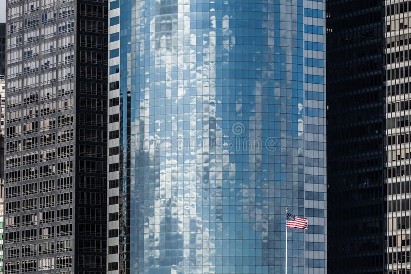 Skyscraper background with US flag in New York City. Modern skyscraper background and US flag in Manhattan, New York City royalty free stock images