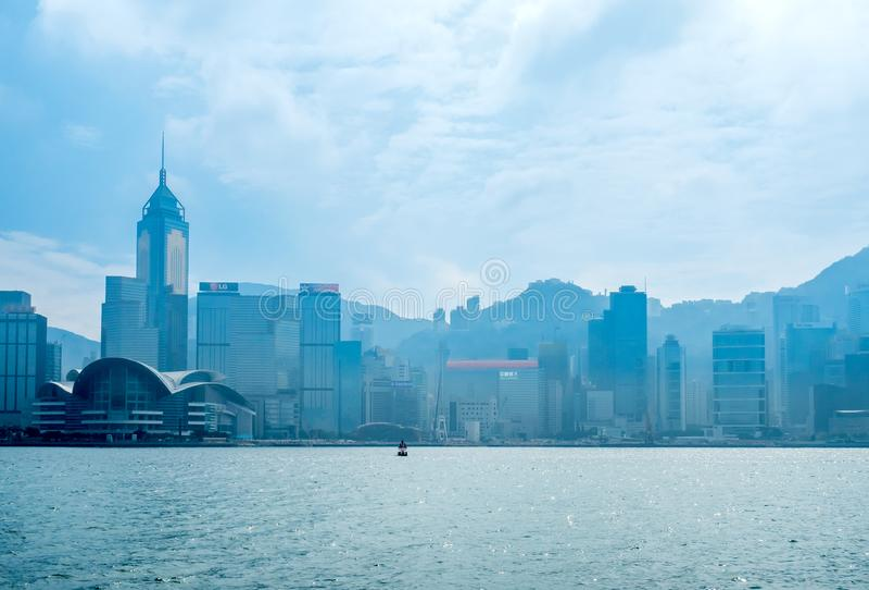 Skyscraper buildings at Victoria harbor, Hong Kong. HONG KONG, CHINA - JANUARY 20 : Landmark skyscraper buildings at Victoria harbor with daylight mist, Hong royalty free stock images