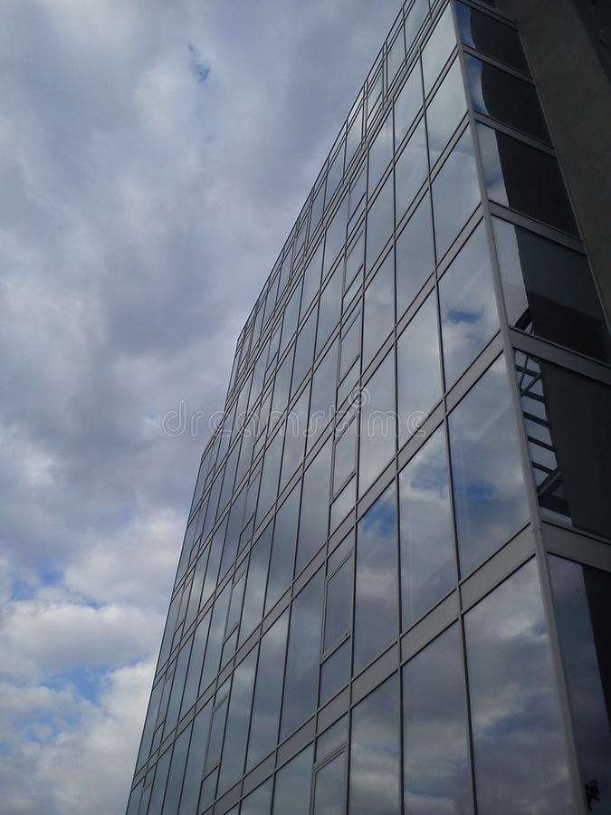 Skyscraper with glass walls and windows. The glass reflects the blue sky and white clouds. Look up royalty free stock image