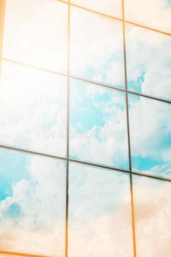 A skyscraper or modern building in a city with clouds and sunlight reflected in the Windows stock images