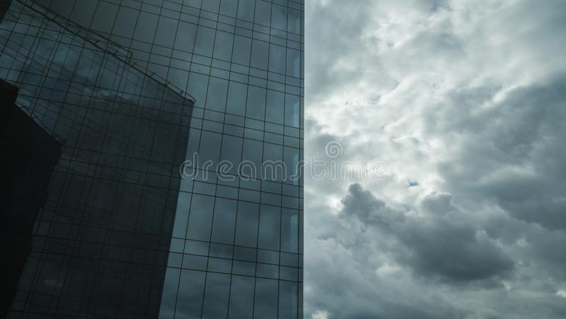 Skyscraper and overcast sky. Modern skyscraper with glassy facade and overcast sky. Office building exterior royalty free stock image