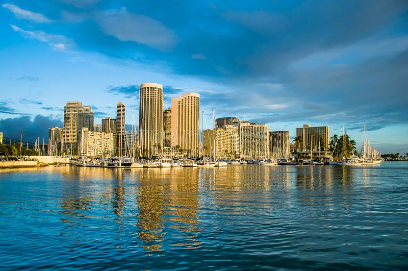 Sunset reflections of Honolulu, Hawaii. The skyscrapers and boats along the harbor are illuminated in golden sunlight as the sun sets over the Pacific Ocean in royalty free stock image