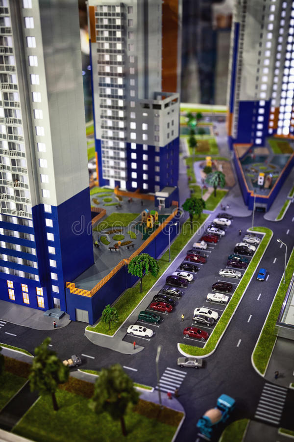 Skyscrapers building project design. Group of miniature house models in an investment exposition. Shallow focus on a car parking stock photography