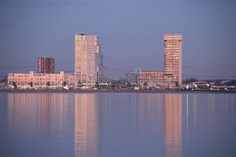 Skyscrapers of the Nesselande residential district of Rotterdam reflecting in Zevenhuizerplas by sunset in the Netherlands seen at stock image