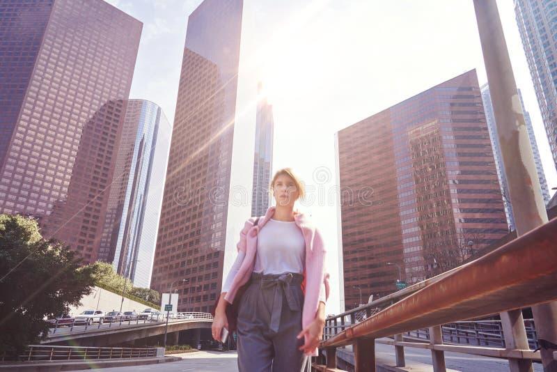 Skyskrapabyggnader och himmelsikt och kvinna som går vid stadsvägen som göras suddig arkivbild