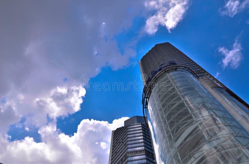 Skyskrapor. Se upp till en djupblå middaghimmel med moln och Sunburst royaltyfri fotografi