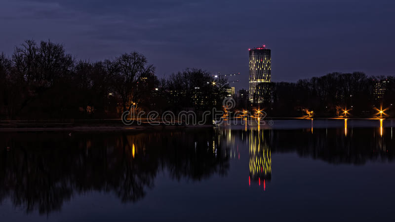 Sky Tower. Bucharest at sunset reflected in Floreasca lake stock image