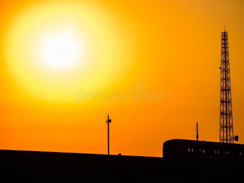 Skytrain ως σκιαγραφία με το όμορφο χρυσό φως του ήλιου και το θερμό πορτοκαλή ουρανό τόνου στοκ εικόνες