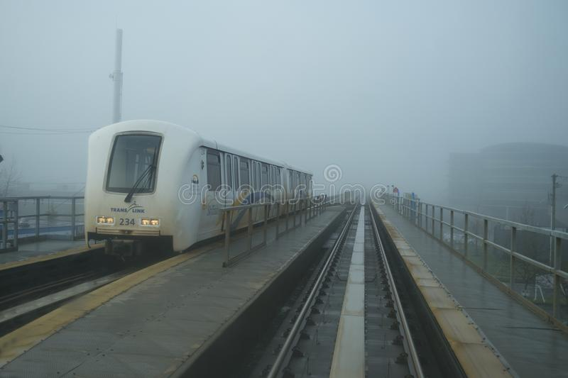 Skytrain mass transit in Vancouver, BC, in fog. Cars run along tracks on the kytrain subway system in Vancouver, Canada, in fog royalty free stock photography