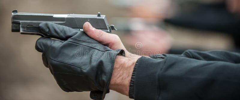Skytt i vapen och skytte för radgrupp människorhåll arkivbild