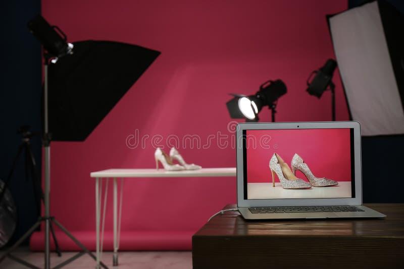 Skytte av kvinnors skor för produkt i fotostudion, fokus på bärbara datorn royaltyfri bild