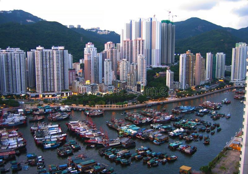 Skyview av de högväxta byggnaderna och de lilla fiskebåtarna i Hong Kong royaltyfri foto