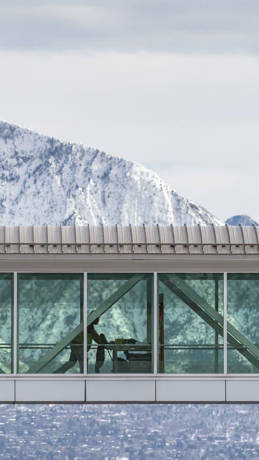 Skyway vertical clair entre les bâtiments avec vue sur la montagne neigeuse et le ciel nuageux en hiver photographie stock