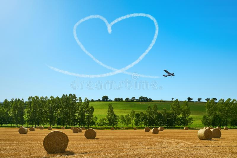 Skywriter dipinge il cuore a cielo per amore immagine stock