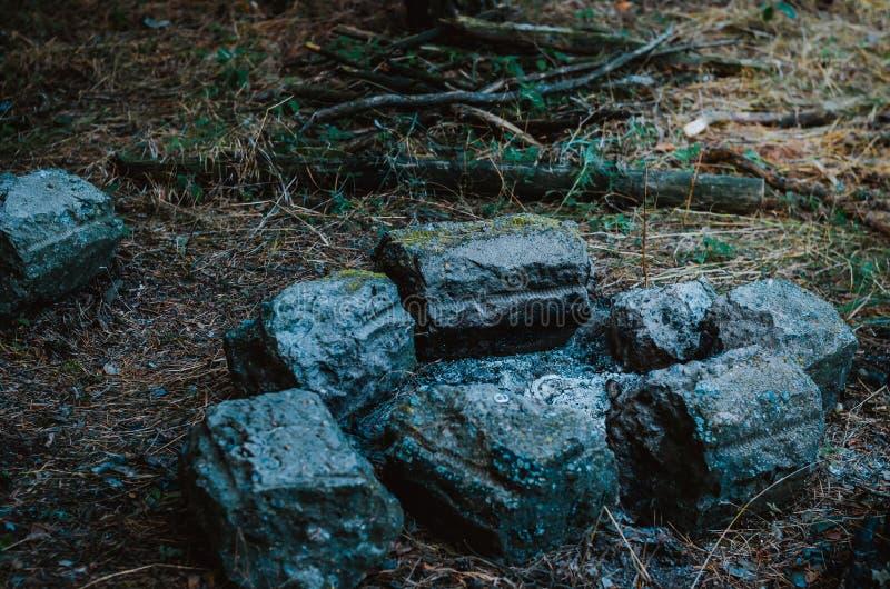 Släckt brasa i det turist- lägret Lägereldplatsen fäktas med stenar Sen afton Vedtr? i bakgrunden Utan p royaltyfria foton