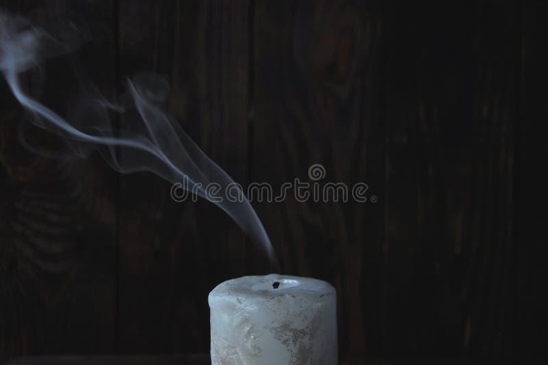 Släckt stor vit stearinljus i mörkret P? en tr?bakgrund royaltyfri bild