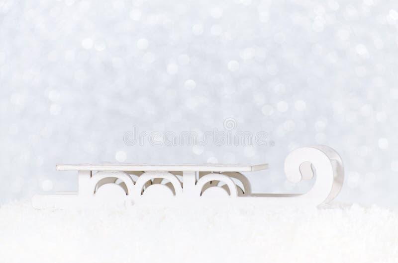 Släde för jultomten` s i snö på bakgrund för vit jul med bokeh arkivbild